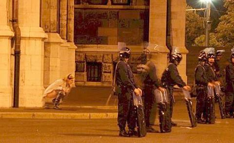 woman squatting to pee behind some riot cops