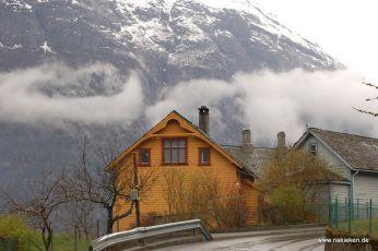 Haus vor den mit Schnee bedeckten Bergen
