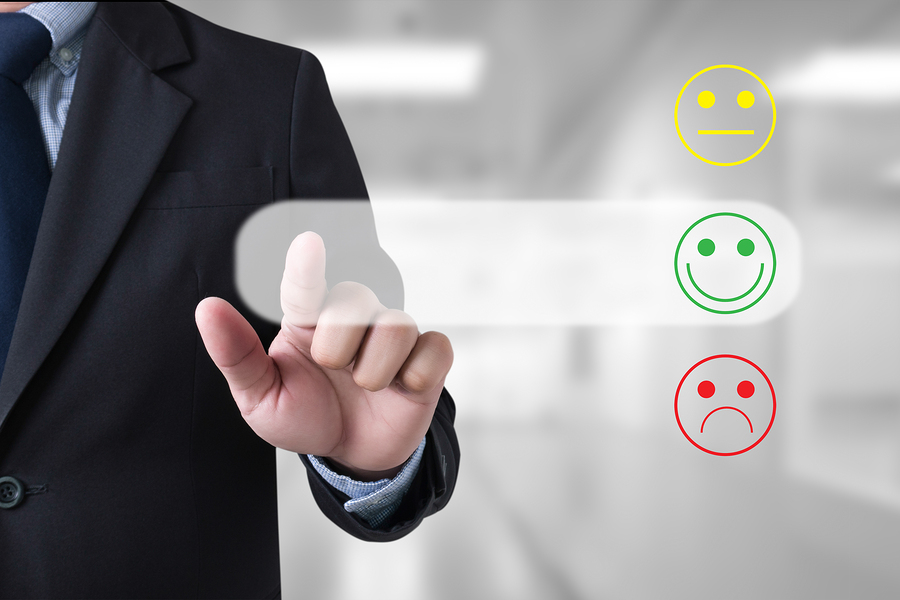 user selecting a happy face on a survey
