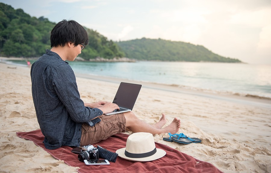 young digital nomad working on laptop on the beach