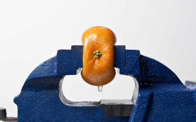 Orange being compressed in a vise