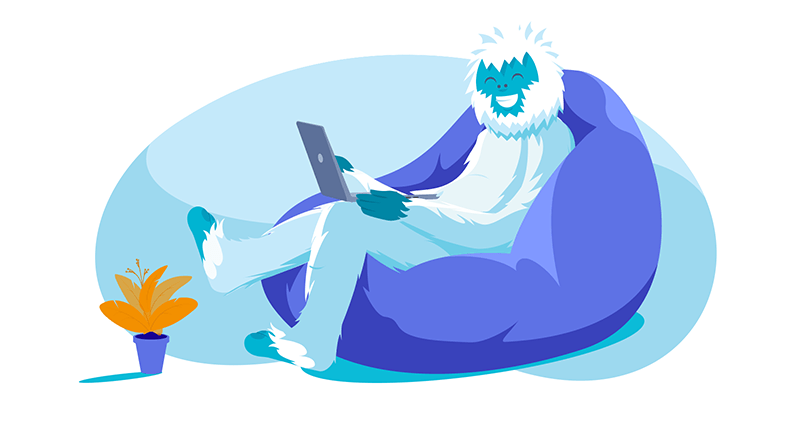 Yeti lounging in bean bag chair working on laptop