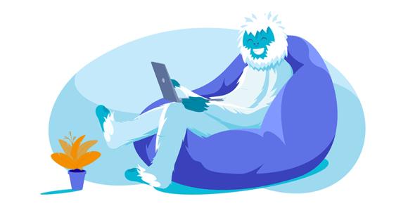 Yeti lounging in bean bag chair working on laptop