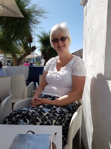 Nancy sitting at a seafront restaurant in Gijon