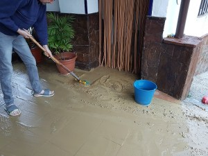 Sweeping up mud from a tiled terrace floor