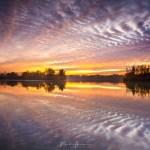 Na zonsondergang, in het windstille moment voor het vallen van de avond, reflecteren de wolken in het water