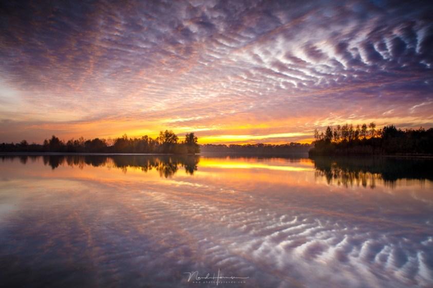Na zonsondergang, in het windstille moment voor het vallen van de avond, reflecteren de wolken in het water - grijsverloopfilters of geen toch geen filters