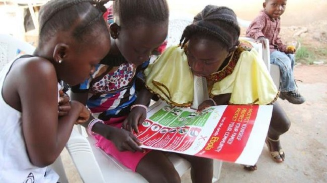 Girls look at a poster, distributed by UNICEF, bearing information to prevent the spread of Ebola