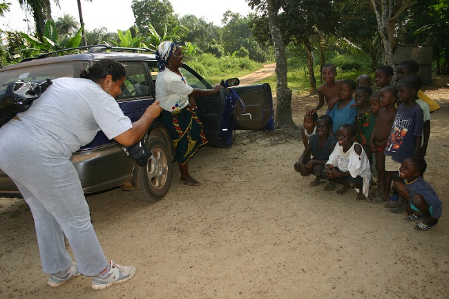 Musue (left) holding a camera as usual, ready to photograph a group of kids at Behsao National Cultural village in Bomi, Liberia. Disembarking the vehicle (in photo) is Liberia's legendary traditional folk singer, Ma-Yata Zoe
