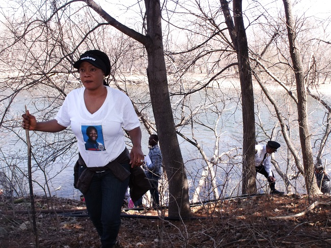 Yarmah Collins walks away from the Mississippi to check residents' backyards for any trace of her stepson Barway