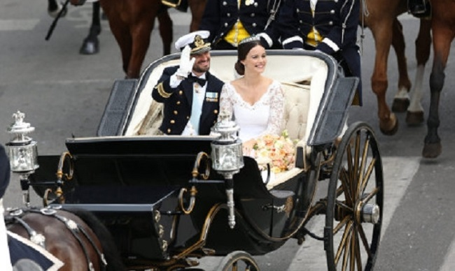Prince Carl Philip and Sofia Hellqvist wave to the crowds from a carriage. Photo: Björn Larsson/TT