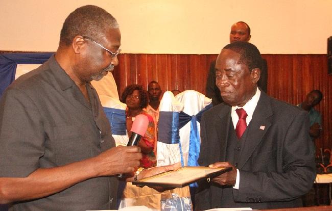 Dr. Jones presents a certificate to Mr. Bestman