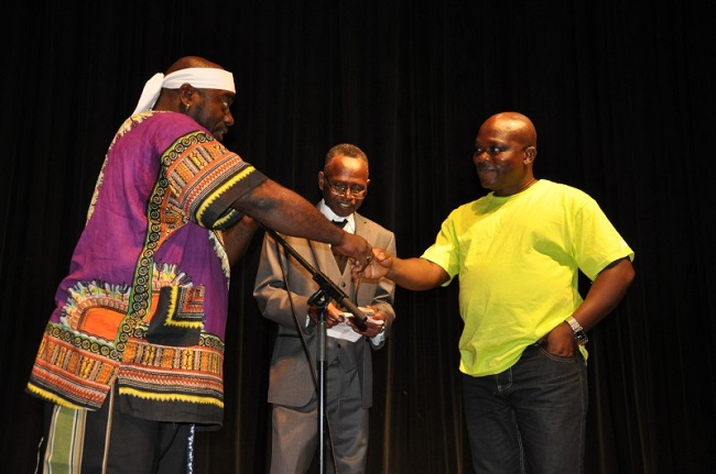Francis Nimely Vinney Napla (l), Artistic Director, Liberian National Cultural Ambassadors, greets Andrew Tehmeh (r), Deputy culture minister. Jallah Koromah (c). Photo: Issa Mansaray/The AfricaPaper