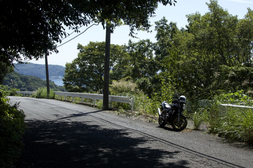 Motorbike by the side of the road in a quiet hillside