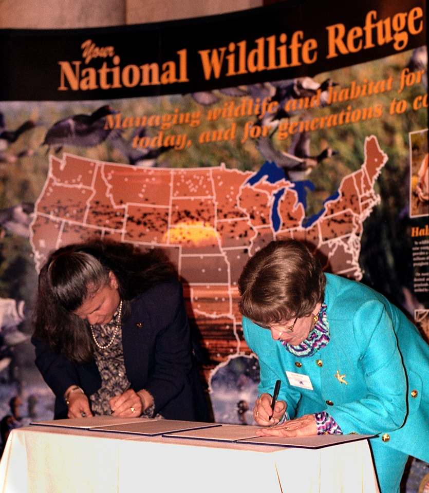 October 8, 1997, Senate Office Building, Washington, DC; U.S. Fish & Wildlife Service Director Jamie Rappaport Clark and NANPA President Jane Kinne sign a Memorandum of Understanding, leading to establishment of NANPA-sponsored photo blinds in national wildlife refuges.