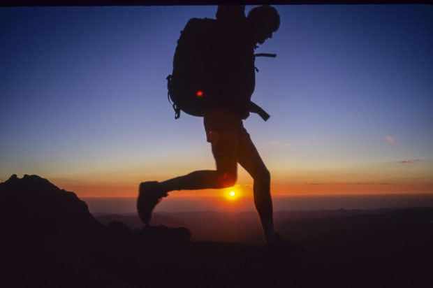 Hiker leaping over the rising sun, Mt. Evans, CO.