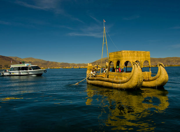 Reed boat from Islas Uros ply the calm waters of Lake Titicaca, Peru.