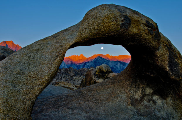Mobius Arch frames Mt. Whitney at sunrise under a full moon.