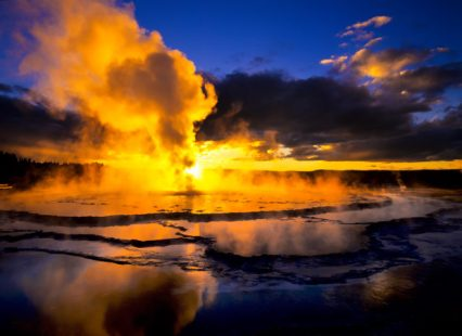 Great Fountain Geyser erupting at sunset in Yellowstone National Park, WY.