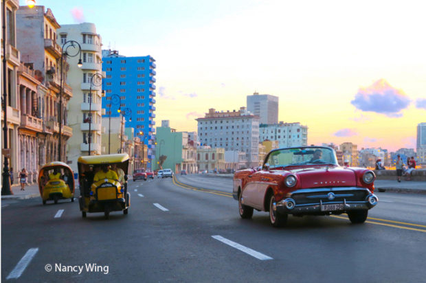 A view, at dusk, of the Havana waterfront—El Malecon—taken from the seat of a Coco taxi or tuk tuk. Paint is used heavily to brighten and enliven the buildings. © Nancy Wing