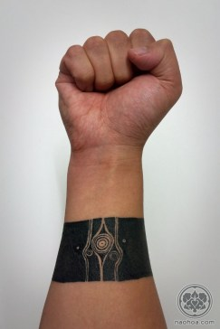 A solid black band around the wrist/forearm. Designed by Monument Valley artist Ken Wong and tattooed by Naomi Hoang, NAOHOA Luxury Bespoke Tattoos, Cardiff, Wales (UK).