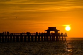 Sunset In Naples Florida. With Pier-Cottage- In The Foreground