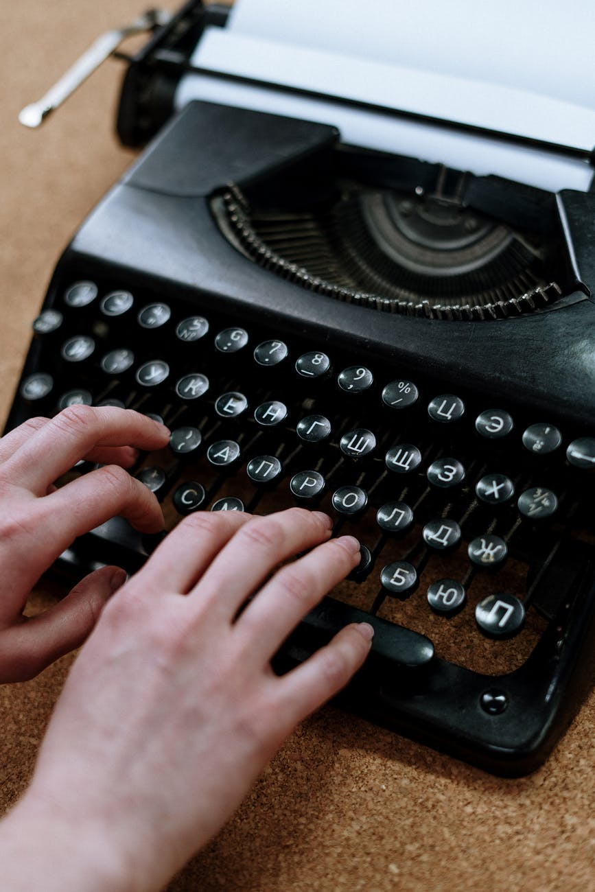 person holding black typewriter on brown table