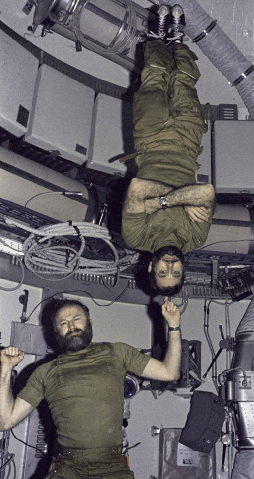 Gerald Carr demonstrates weight training in zero gravity by balnacing felkow astronaut William Pogue upside down on his finger.