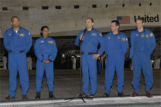 Five STS-116 crew members stand beside Discovery after landing at Kennedy Space Center.