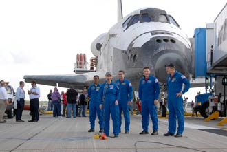 The crew of STS-120 in front of Discovery.