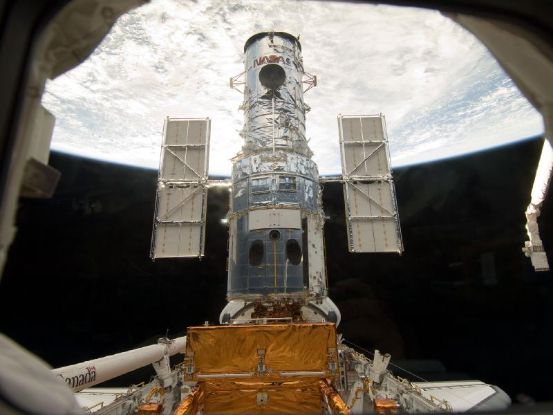 Hubble attached to the shuttle bay with the Earth in the background