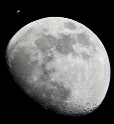 JSC2012-E-017827 -- International Space Station can be seen as a small object in upper left of this image of the moon