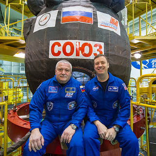 In the Integration Building at the Baikonur Cosmodrome in Kazakhstan, Expedition 51 crewmembers Fyodor Yurchikhin of the Russian space agency Roscosmos and Jack Fischer of NASA sit for pictures April 6, 2017, in front of their Soyuz MS-04 spacecraft as part of pre-launch preparations. Credits: NASA