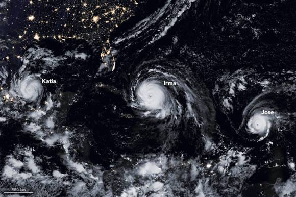 Satellite image at night showing cities lights in the southern U.S. at the top of the image and beneath over the Gulf of Mexico three hurricanes in a row: from left to right Katia, Irma, and Jose.