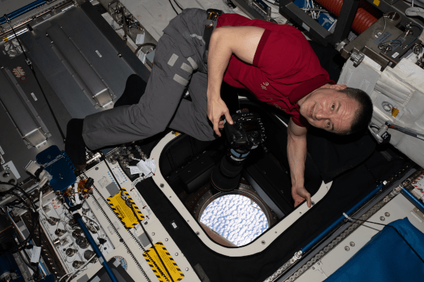 astronaut andrew morgan taking pictures from inside of the space station