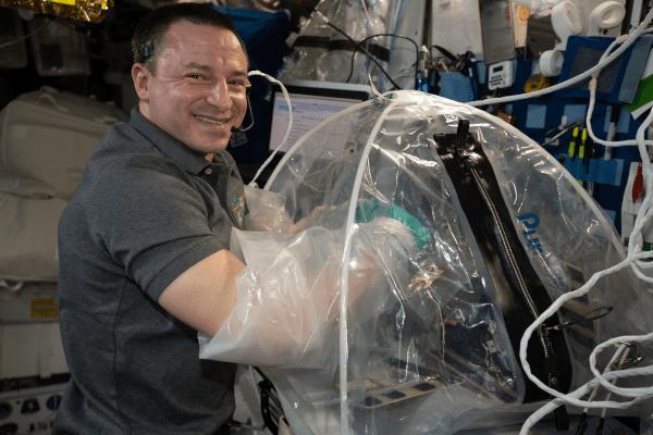 astronaut andrew morgan working inside a glove bag