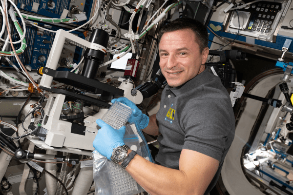 astronaut andrew morgan running science experiments inside the space station