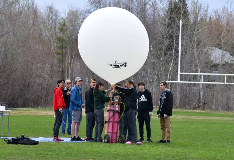 Students stand outside by a weather balloon that they're about to launch