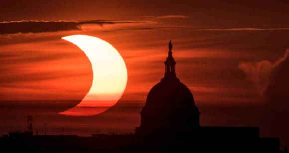 """A partial solar eclipse is seen as the sun rises to the left of the United States Capitol building, Thursday, June 10, 2021, as seen from Arlington, Virginia. The annular or """"ring of fire"""" solar eclipse was visible in the far northern hemisphere."""