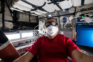 astronaut Sochi Noguchi inspecting inside of Dragon spacecraft