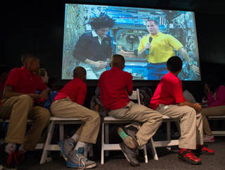 International Space Station Expedition 33 crew (on screen) answers questions from students during a downlink event