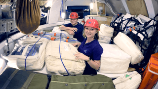 Two women wearing hard hats are in small bay of a spacecraft, surrounded by storage bags.