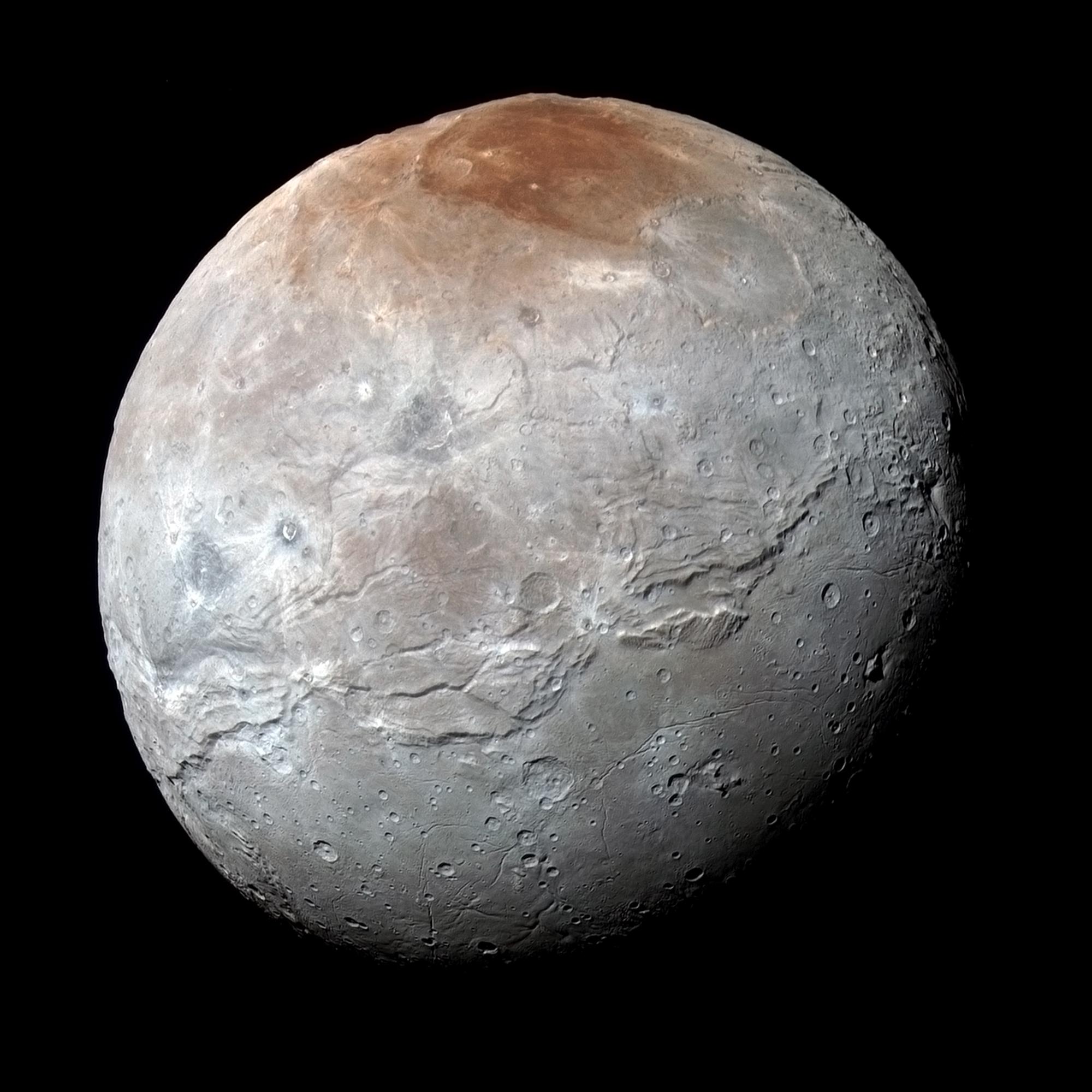 La nave New Horizons de NASA captó esta imagen de alta resolución en color realzado de la mayor luna de Plutón, Caronte. Los científicos han averiguado que el material rojizo de la región polar norte (llamada informalmente Mordor Macula) es metano procesado químicamente que escapó de la atmósfera de Plutón y llegó a Caronte. Crédito: NASA/JHUAPL/SwRI.
