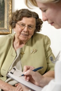 VNA Nurse with clipboard taking notes with a patient