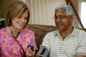 Home care nurse with African American elderly man taking blood pressure