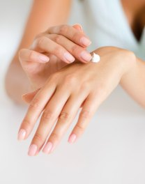 Woman applying lotion on her hand