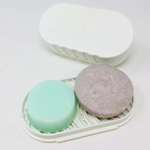 A bar of shampoo and a bar of conditioner for curly and dry hair sitting on a white, recycled plastic travel case soap tray.