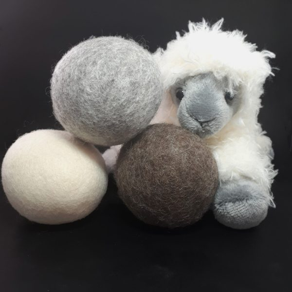 Three wool dryer balls: One grey, one brown and one white, stacked in a triangle. They are beside a white plush toy sheep