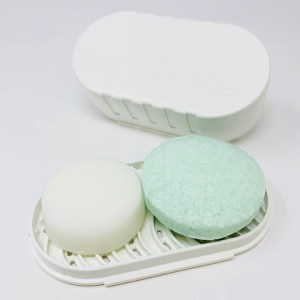 A bar of shampoo and a bar of conditioner for oily hair sitting on a white, recycled plastic travel case soap tray.