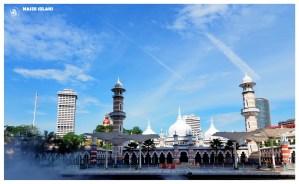 Kuala Lumpur Malezja, plac przed meczetem Jamek, słoneczny dzień, na placu parasole chroniące przed słońcem, upalne przedpołudnie, błękitne niebo,